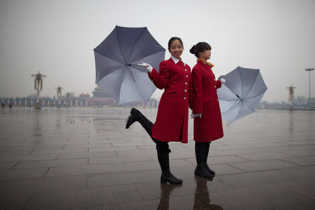 A hostess (L) poses on Tiananmen Square as they wait for delegates to return from the closing session of the Chinese People's Political Consultative Conference (CPPCC) at the Great Hall of the People in Beijing. Thousands of delegates from across China met this week to seal a power transfer to new leaders whose first months running the Communist Party have pumped up expectations with a deluge of propaganda. (Photo by Ed Jones)