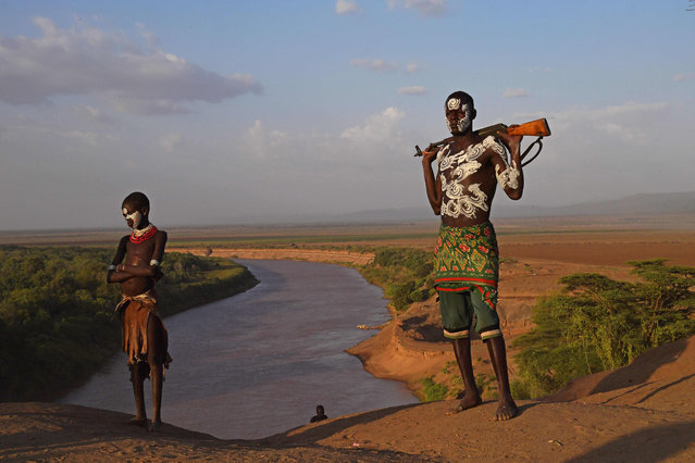 """Members from the Karo tribe pose in front of the Omo river in Ethiopia's southern Omo Valley region on September 23, 2016. The Karo are a Nilotic ethnic group in Ethiopia famous for their body painting. They are also one of the smallest tribes in the region. The construction of the Gibe III dam, the third largest hydroelectric plant in Africa, and large areas of very """"thirsty"""" cotton and sugar plantations and factories along the Omo river are impacting heavily on the lives of tribes living in the Omo Valley who depend on the river for their survival and way of life. Human rights groups fear for the future of the tribes if they are forced to scatter, give up traditional ways through loss of land or ability to keep cattle as globalisation and development increases. (Photo by Carl De Souza/AFP Photo)"""