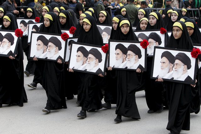 Girls carry portraits of Iran's late leader Ayatollah Ruhollah Khomeini and Supreme Leader Ayatollah Ali Khamenei during the funeral of three Hezbollah fighters who were killed while fighting alongside Syrian army forces in Syria in Nabatieh town, southern Lebanon, October 27, 2015. (Photo by Ali Hashisho/Reuters)