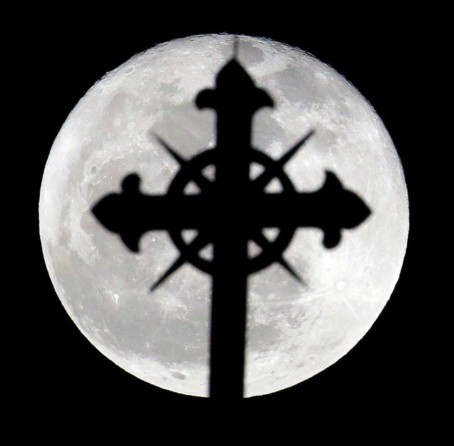 A full moon rises behind a cross on top of Saint Nicholas Catholic Church in the Heights neighborhood of Jersey City, N.J., Wednesday, March 27, 2013. Catholics are observing Holy Week, which is the final week of the Lent period before Easter. (Photo by Julio Cortez/AP Photo)