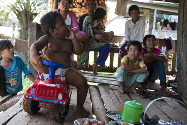 Aldi SugandaRizal (2 years-old) smoking a cigarette while playing at the family home in Sekayu district, South Sumatera, Indonesia on May 23, 2010. (Photo by Ardiles Rante/Barcroft Media)