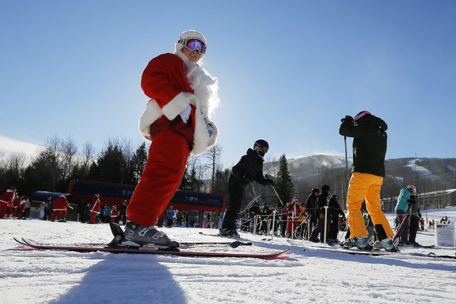 A skier dressed as Santa Claus prepares to participate in a charity run down a slope at Sunday River Ski Resort in Newry, Maine December 7, 2014. (Photo by Brian Snyder/Reuters)