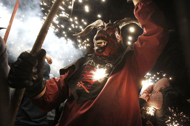 "A reveler wearing a demon costume takes part in the traditional festival of ""Correfoc"" in Palma de Mallorca, on January 21, 2013. Participants dress as demons and devils and move through the streets scaring people with fire and fireworks. (Photo by Jaime Reina/AFP Photo /The Atlantic)"