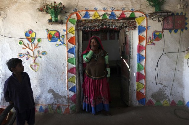 Tulsi, who is cotton picker, stands in the doorway of her room which is decorated with coloured patterns, in Meeran Pur village, north of Karachi November 23, 2014. (Photo by Akhtar Soomro/Reuters)