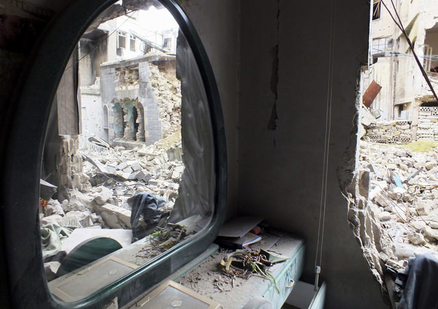 A mirror stands inside an old damaged house in Homs, on March 16, 2013. (Photo by Yazen Homsy/Reuters /The Atlantic)