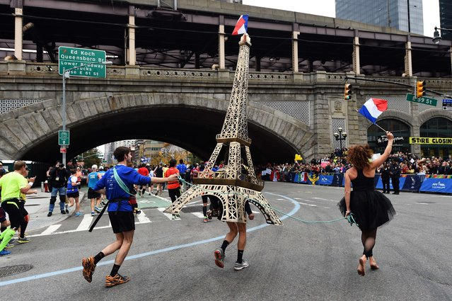 A runner carries a model of Eiffel Tower during the TCS New York City Marathon in New York on November 1, 2015. (Photo by Jewel Samad/AFP Photo)