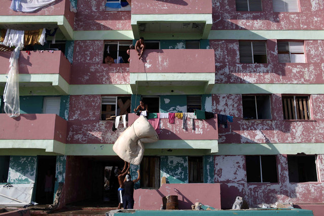 People lower a mattress from a balcony after the passage of Hurricane Matthew in Baracoa, Cuba October 7, 2016. (Photo by Alexandre Meneghini/Reuters)