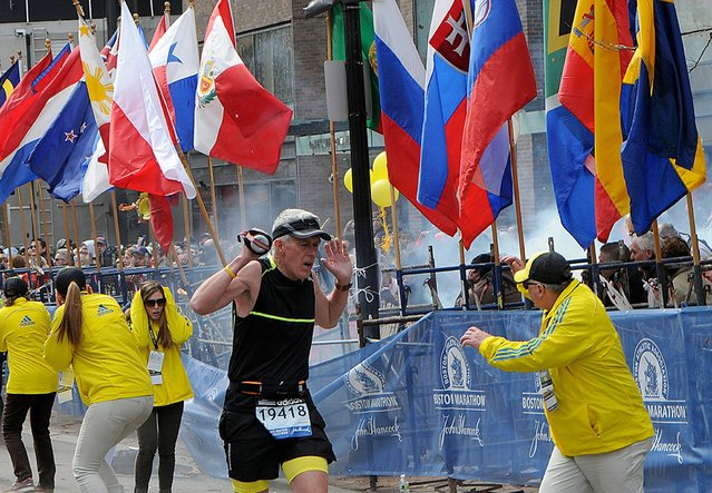 A runner and race officials react to an explosion during the Boston Marathon in Boston, Massachusetts, April 15, 2013. (Photo by Ken McGagh/Reuters/MetroWest Daily News)