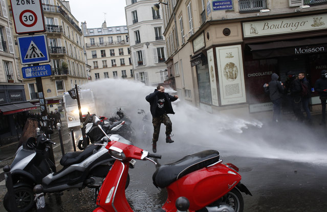 A man jumps to avoid a police water canon during a demonstration, Thursday, March 22, 2018 in Paris. Nationwide strikes are causing major disruptions to trains, planes, schools and other public services in France Thursday as unions set up dozens of street protests across the country. Paris protest was mostly peaceful, but some localized scuffles broke out between some violent protesters wearing black hoods and riot police. (Photo by Thibault Camus/AP Photo)