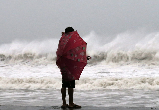 A Filipino resident watches strong waves at a coastal village in Borongan city, Samar island, Philippines, December 6, 2014. Typhoon Hagupit is speeding up and expected to make landfall in the eastern Philippines later December 6, a senior weather official said. (Photo by Francis R. Malasig/EPA)