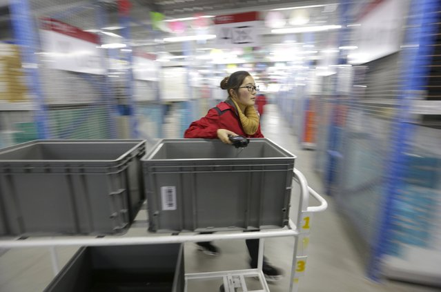 An employee works at a JD.com logistic centre in Langfang, Hebei province, November 10, 2015. On China's giant Singles Day internet shopping festival, the country's delivery firms are stretched so thin that they are looking for tie-ups, listings and new investors to husband their resources. (Photo by Jason Lee/Reuters)
