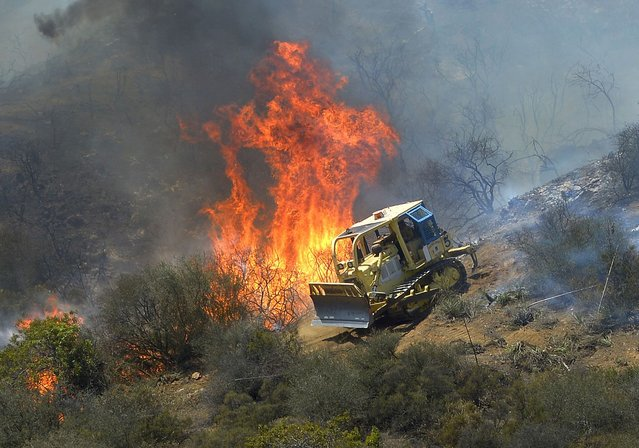 A bulldozer clears a firebreak near a wildfire burning along a hillside near homes in Thousand Oaks, Calif., Thursday, May 2, 2013. A Ventura County Fire Department spokeswoman said the blaze that broke out Thursday morning near Camarillo and Thousand Oaks, 50 miles west of Los Angeles, had spread to over 6,500 acres, forcing evacuations of nearby neighborhoods. (Photo by Mark J. Terrill/AP Photo)