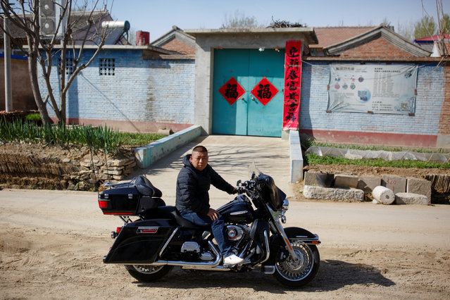 """Guo Qingshan poses on his Harley-Davidson motorcycle in his village outside Beijing, China on April 19, 2018. """"I love the sound of the engine and the muscle of the motor. When I ride it, I feel free and proud"""", Guo said. However, Guo has his limits. If prices rise, Guo said he wouldn't contemplate buying another Harley. (Photo by Thomas Peter/Reuters)"""
