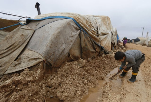 An internally displaced child plays with water and mud outside tents at the Bab Al-Salam refugee camp in Azaz, near the Syrian-Turkish border December 28, 2014. (Photo by Hosam Katan/Reuters)