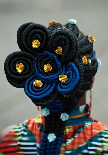 A woman presents an Afro-Colombian hairstyle during the 9th contest of Afro-hairdressers, in Cali, Valle del Cauca departament, Colombia, on May 12, 2013. The Afro hairstyles have their origins in the time of slavery, when women sat to comb their children hair after work. (Photo by Luis Robayo/AFP Photo)
