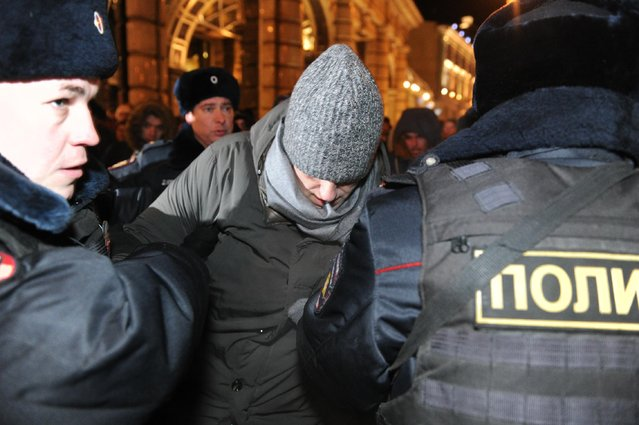 Police officers detain Russian opposition activist and anti-corruption crusader Alexei Navalny, 38, center, on his way to attend a rally in Manezhnaya Square in Moscow, Russia, Tuesday, December 30, 2014. (Photo by Anton Belitskiy/AP Photo)