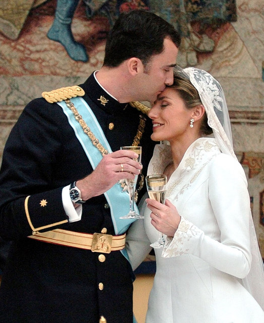 Spanish Crown Prince Felipe kisses the forehead of his bride Letizia Ortiz, Princess of Asturias, at the start of the wedding banquet at Madrid's Royal Palace, May 22, 2004. Prince Felipe married former television presenter Ortiz in a glittering ceremony symbolizing a new dawn for Spain two months after the deadly Madrid train bombings. (Photo by Reuters/Ballesteros)