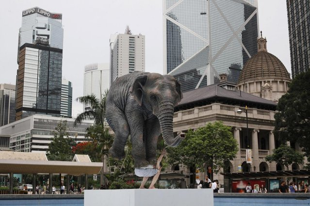 "A five meters high sculpture ""Pentateuque"" created by Contemporary French artist Fabien Merelle, is displayed in Central, business district of Hong Kong, Tuesday, May 21, 2013. The artwork brings to real life the fantastical and seemingly impossible act of an average man balancing a gigantic elephant. The elephant and the man are modeled on one at the Singapore Zoo and on the artist himself. (AP Photo/Kin Cheung)"
