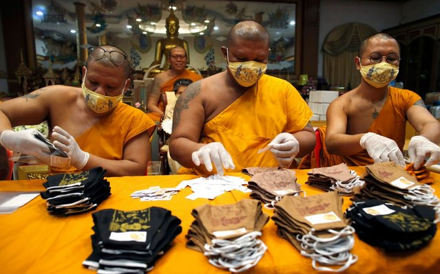 Thai Buddhist monks pack face masks inscribed with spiritual incantations at Wat Phai Lom in Nakhon Pathom province, Thailand, 29 March 2020. The face masks made by villagers are inscribed with spiritual incantations by Thai Buddhist monk Phra Kru Palad Sitthiwat, known as Luang Phi Namfon, the abbot of Wat Phai Lom, and sold by him, aimed to protect devotees from the growing fear of people in the wake of the coronavirus COVID-19 pandemic. More than 100,000 of the talisman protective masks have been sold across Thailand. Seven people have died in the country since the beginning of the coronavirus outbreak, and more than 1,300 COVID-19 infections have been reported so far. (Photo by Rungroj Yongrit/EPA/EFE)