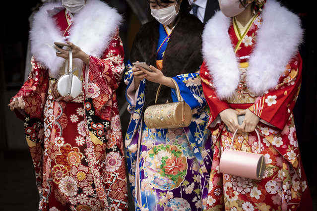 "Twenty-year-old women dressed in kimonos leave Todoroki Arena during the ""Coming-of-Age Day"" celebration ceremony in Kawasaki, Kanagawa prefecture on January 11, 2021 under a state of emergency over the Covid-19 coronavirus pandemic. (Photo by Behrouz Mehri/AFP Photo)"