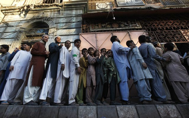 Men and children queue up to get charity food distributed to mark Eid-e-Milad-ul-Nabi, the birth anniversary of Prophet Mohammad, in Karachi January 4, 2015. (Photo by Akhtar Soomro/Reuters)