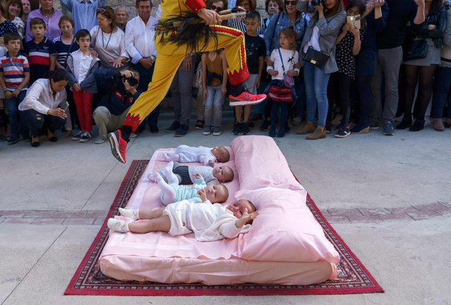 "The""'Colacho"" (man representing the devil) jumps over babies during ""El salto del Colacho"", the baby jumping festival in the village of Castrillo de Murcia, near Burgos on June 3, 2018. Baby jumping (El Colacho) is a traditional Spanish practice dating back to 1620 that takes place annually to celebrate the Catholic feast of Corpus Christi. During the act – known as El Salto del Colacho (the devil's jump) or simply El Colacho – men dressed as devils jump over babies born in the last twelve months of the year who lie on mattresses in the street. (Photo by Cesar Manso/AFP Photo)"