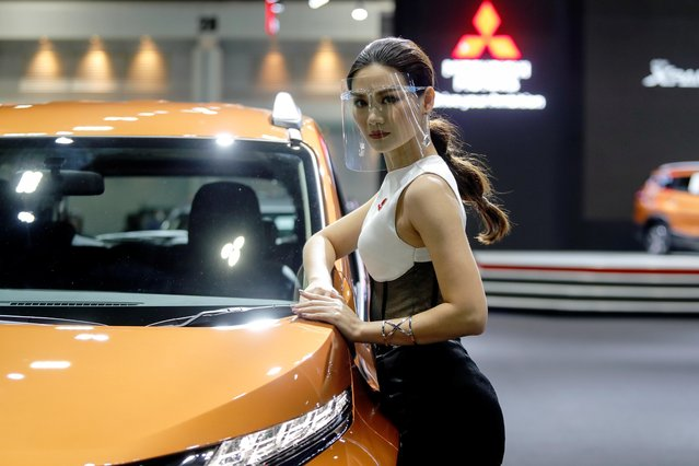 A model wearing a face shield poses with a Mitsubishi vehicle during the media day of the 41st Bangkok International Motor Show after the Thai government eased measures to prevent the spread of the coronavirus disease (COVID-19) in Bangkok, Thailand on July 14, 2020. (Photo by Jorge Silva/Reuters)