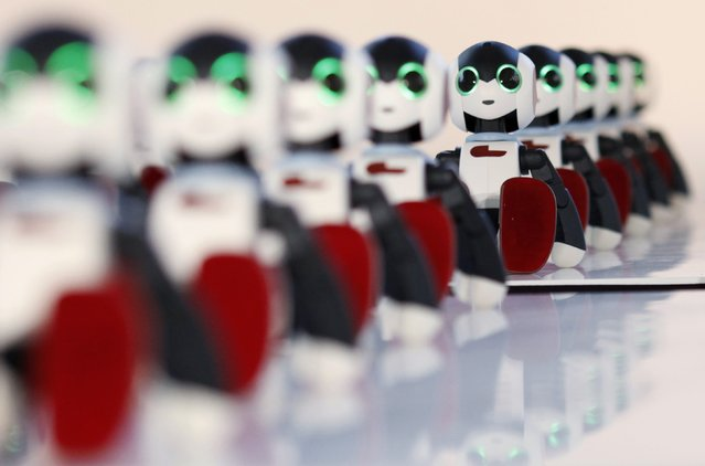 """A hundred humanoid communication robots called """"Robi"""" sit before a dance performance dance during a promotional event called 100 Robi, for the Weekly Robi Magazine, in Tokyo January 20, 2015. (Photo by Yuya Shino/Reuters)"""