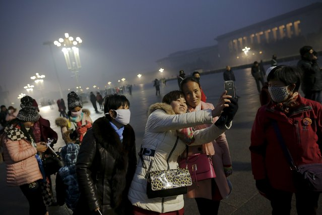 "People gather before sunrise at Tiananmen Square for a flag-raising ceremony amid heavy smog, after the city issued its first ever ""red alert"" for air pollution, in Beijing December 9, 2015. (Photo by Damir Sagolj/Reuters)"