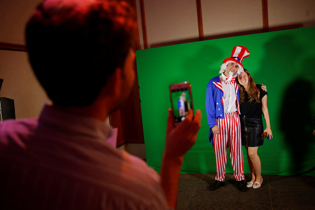 A woman gets her picture taken with a man dressed as Uncle Sam in a U.S. presidential elections night event held by the U.S. Embassy in Tel Aviv, Israel November 8, 2016. (Photo by Baz Ratner/Reuters)