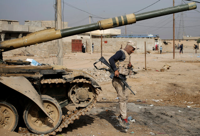 An Iraqi soldier jumps from a tank in a village outside Mosul, Iraq November 9, 2016. (Photo by Goran Tomasevic/Reuters)