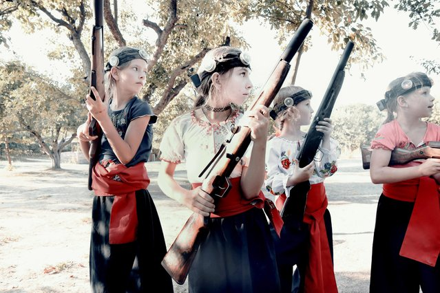 Young girls practice shooting in a Cossack patriotic camp that trains them with weapons and teaches them to hate the Russian influence and all its forms. (Photo by Aude Osnowycz/The Sun)