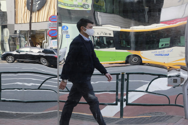A man wearing face masks to protect against the spread of the coronavirus is reflected on mirrors on the wall of a tailor shop in Tokyo, Monday, February 1, 2021. (Photo by Koji Sasahara/AP Photo)