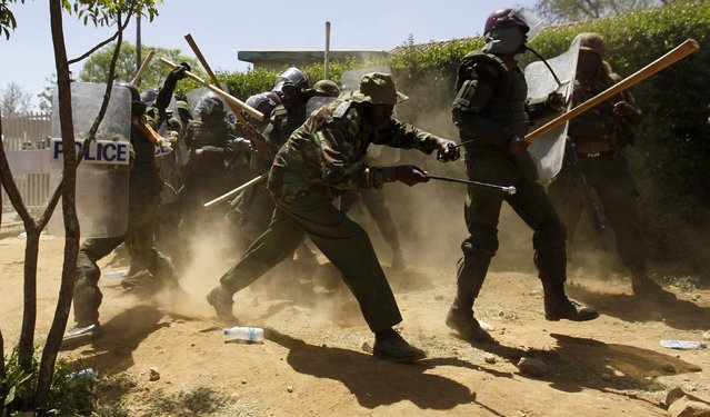 Riot policemen run to take cover after dispersing residents during protests to oust Narok county Governor Samuel Tunai in Narok, Kenya, January 26, 2015. (Photo by Thomas Mukoya/Reuters)