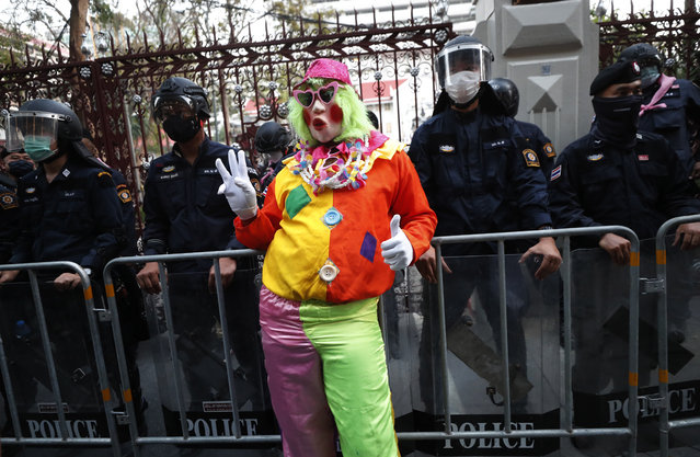 A pro-democracy protester wearing a clown clothing raises a three-finger salute, a symbol of resistance, in front of riot police at Police Headquarter in Bangkok, Thailand, Tuesday, February 23, 2021. (Photo by Sakchai Lalit/AP Photo)
