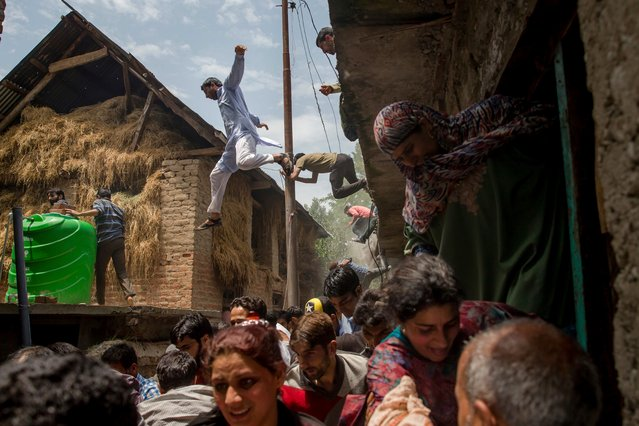Kashmiri villagers inspecting a house damaged in a gun battle flee from it after hearing rumors of Indian army soldiers returning back to the site, which turned out to be false, in Kundalan village, some 60 Kilometres south of Srinagar, Indian controlled Kashmir, Tuesday, July 10, 2018. Government forces fired at protesters Tuesday in Indian-controlled Kashmir, killing a teenage boy and wounding at least 120 more who had been trying to reach the site of a gunbattle in which soldiers killed two rebels, police and residents said. (Photo by Dar Yasin/AP Photo)