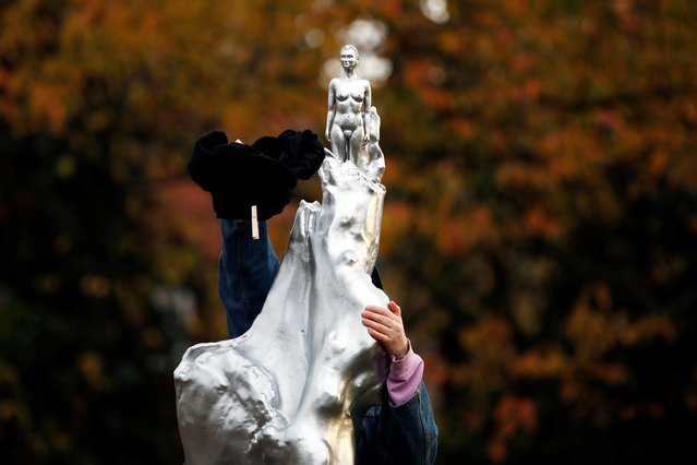 """A person removes a t-shirt from the Mary Wollstonecraft statue """"Mother of feminism"""" by artist Maggi Hambling in Newington Green, London, Britain, November 11, 2020. (Photo by Paul Childs/Reuters)"""