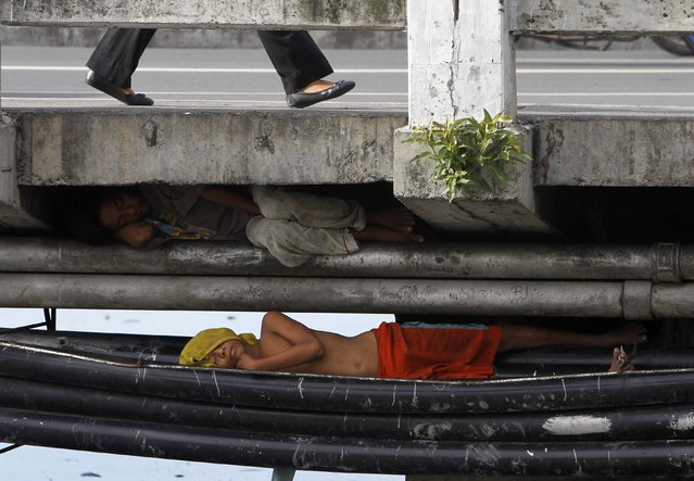 Street children sleep under a bridge in Paranaque city, metro Manila July 18, 2013. Picture taken July 18, 2013. (Photo by Romeo Ranoco/Reuters)