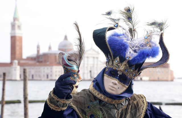A masked reveller poses in front of St. Mark's square during the first day of carnival, in Venice February 1, 2015. (Photo by Stefano Rellandini/Reuters)
