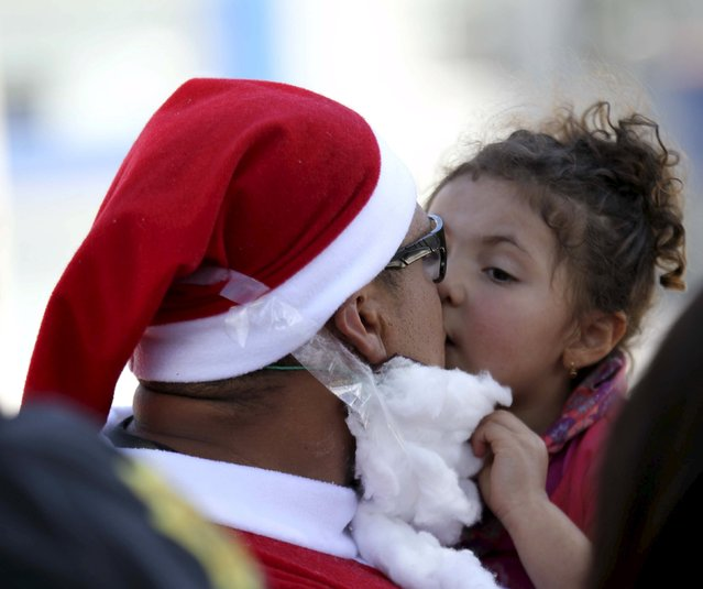 A police officer in a Santa Claus outfit kisses his daugther during a Christmas event for street children in Quito December 22, 2015. (Photo by Guillermo Granja/Reuters)