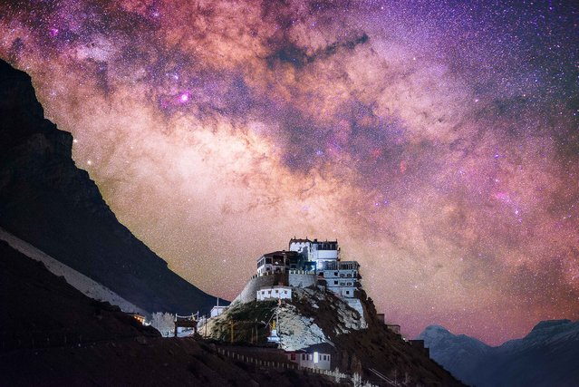 Key Monastery illuminated on a mountain in the Spiti Valley, Himachal Pradesh, northern India with an amazing nights sky illuminated beyond. (Photo by Grey Chow/Caters News Agency)
