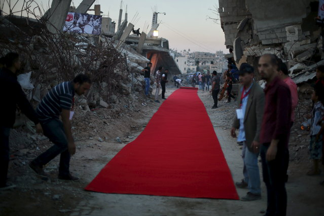 Palestinians place a red carpet between the ruins of houses, that witnesses said were destroyed by Israeli shelling during a 50-day war last summer, before they display a film on the war in the east of Gaza City May 12, 2015. (Photo by Mohammed Salem/Reuters)