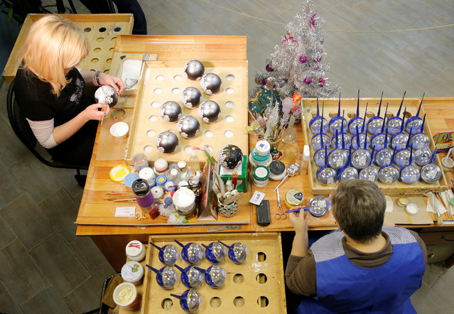 """Employees paint glass Christmas and New Year decorations at the """"Yolochka"""" (Christmas tree) factory, which has been producing glass decorations and toys for the festive season since 1848, in the town of Klin outside Moscow, Russia, November 24, 2016. (Photo by Maxim Zmeyev/Reuters)"""