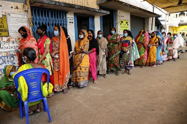 Voters stand in a queue to cast their votes outside a polling booth during first phase of elections in West Bengal state in Medinipur, India, Saturday, March 27, 2021. (Photo by Bikas Das/AP Photo)