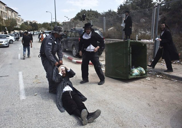 An Israeli policeman drags an ultra-Orthodox man during clashes in the town of Beit Shemesh, near Jerusalem August 12, 2013. An Israeli police spokesperson said some 21 ultra-Orthodox protesters were detained on Monday in the town during clashes with police after a group of them broke into a construction site to prevent work from taking place at the site they believe contains ancient graves. (Photo by Nir Elias/Reuters)