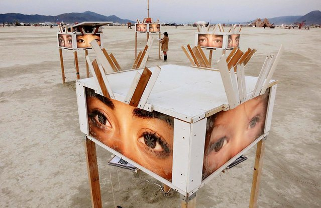 A participant looks at art works on the playa at sunrise. (Photo by Jim Bourg/Reuters)