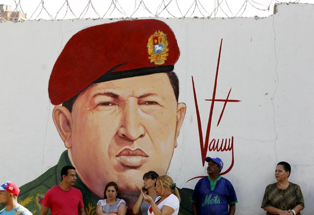 Supporters of Venezuela's President Nicolas Maduro stand in front of a mural depicting Venezuela's late President Hugo Chavez some streets away from the building housing the National Assembly in Caracas, January 5, 2016. (Photo by Christian Veron/Reuters)