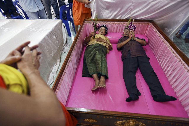 A groom and a bride lay inside a pink coffin during their wedding ceremony at Wat Takien temple in Nonthaburi province, on the outskirts of Bangkok February 14, 2015. (Photo by Damir Sagolj/Reuters)