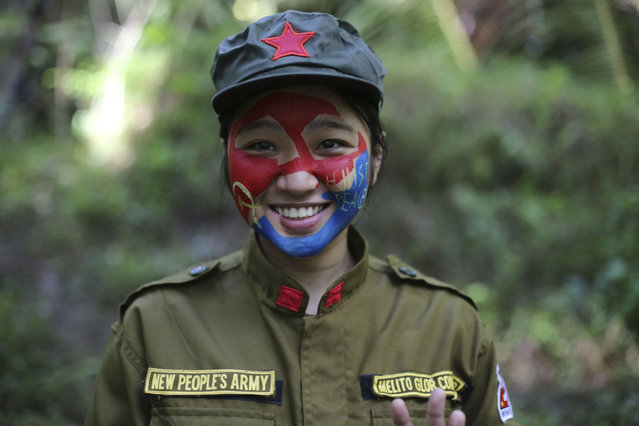 In this photo taken November 23, 2016, a 24-year-old New People's Army guerrilla, who uses the nom de guerre Comrade Katryn, smiles as she talks to reporters at a rebel encampment tucked in the harsh wilderness of the Sierra Madre mountains southeast of Manila, Philippines. Communist guerrillas warn that a peace deal with President Rodrigo Duterte's government is unlikely if he won't end the Philippines' treaty alliance with the United States and resist control by other countries. (Photo by Aaron Favila/AP Photo)