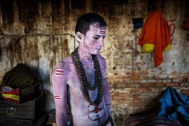 A Sadhu, Hindu holy person, prepares himself by smearing ashes on his body during the Maha Shivaratri festival at the Pashupati Temple in Kathmandu, Nepal, 11 March 2021. The Maha Shivratri festival, which is celebrated on 11 March, sees Hindu devotees, from across the country and neighboring India, gather to celebrate the birthday of Lord Shiva, the Hindu god of creation and destruction, by offering special prayers and fasting. (Photo by Narendra Shrestha/EPA/EFE)